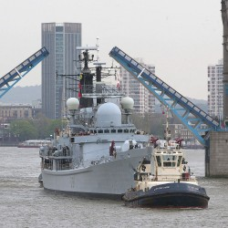 HMS Edinburgh is assisted by a tug under Tower Bridge on the River Thames during her final visit to the capital before decommisioning.